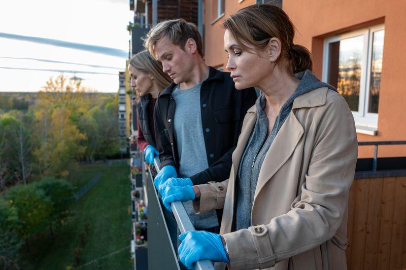 Am Tatort: Die Kommissare Pia (Annika Blendl, links), Linus (Anton Spieker) und Maike (Anja Kling) blicken vom Balkon eines Studentenwohnheims, von dem eine Doktorandin in die Tiefe gefallen ist.